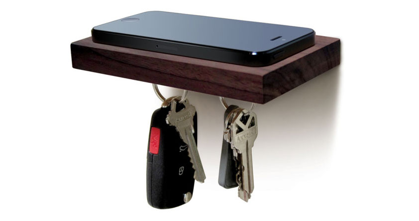 Dark brown wooden plank board that holds keys with magnets