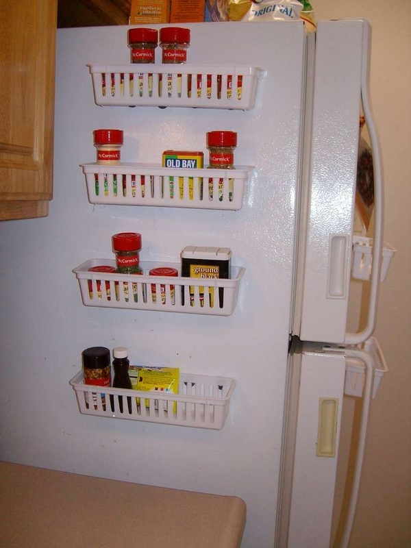 3M command strips holding up storage for spices on the side of a fridge