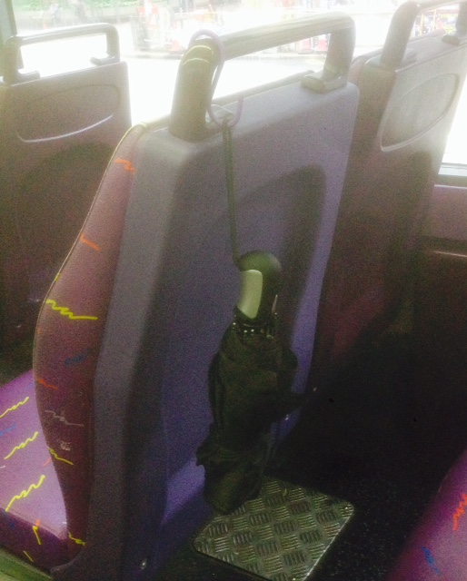 S hook holding an umbrella on the back of a bus seat