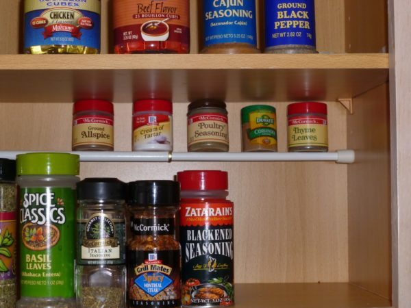 Spices on tension rod to create a second level in the pantry
