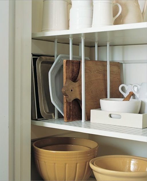 Tension rods dividing chopping boards on pantry shelf