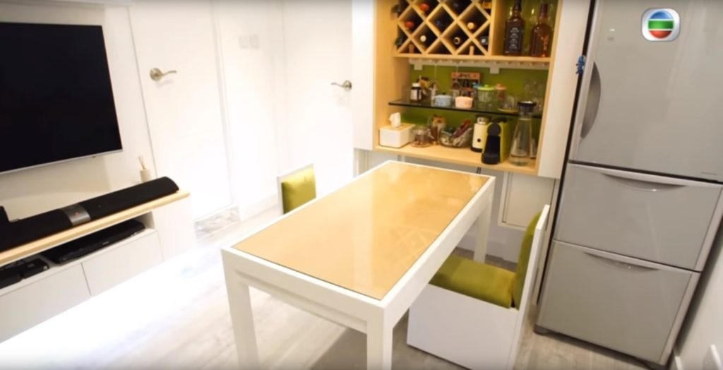 White table with wooden top and two dining chairs that pull out
