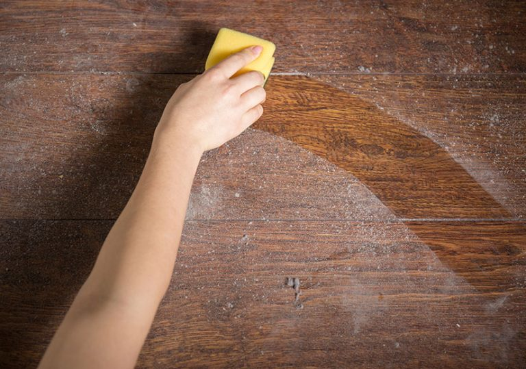 Wiping dust away from wooden table